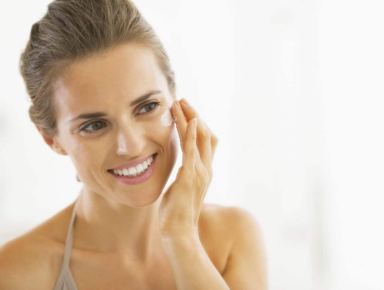 Person applying a cream on their cheek
