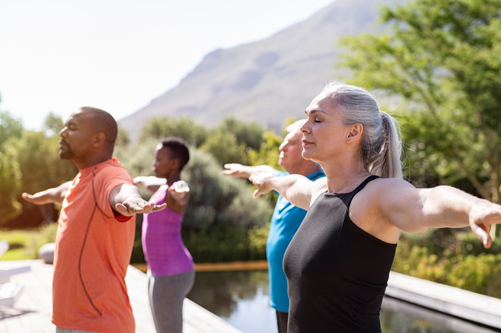 A group of adults doing a yoga pose outside in front of a mountain
