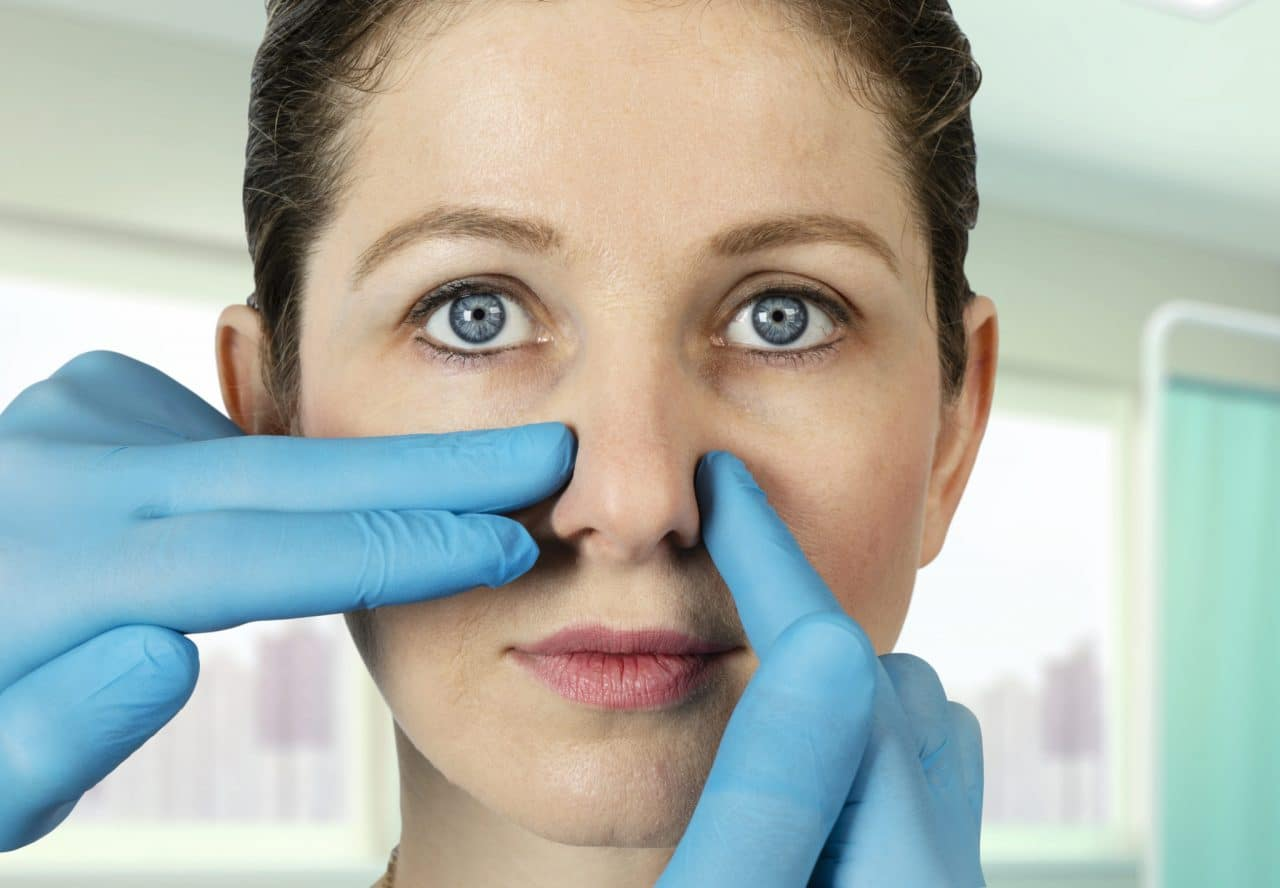 A person having their nose examined by touch