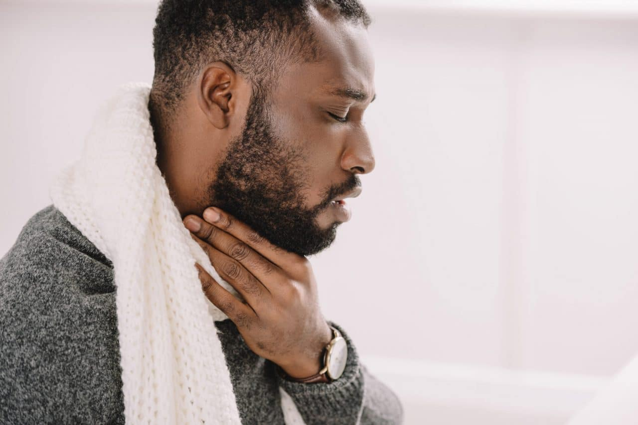 Photo of a person wearing a scarf and sweater and holding their throat in discomfort