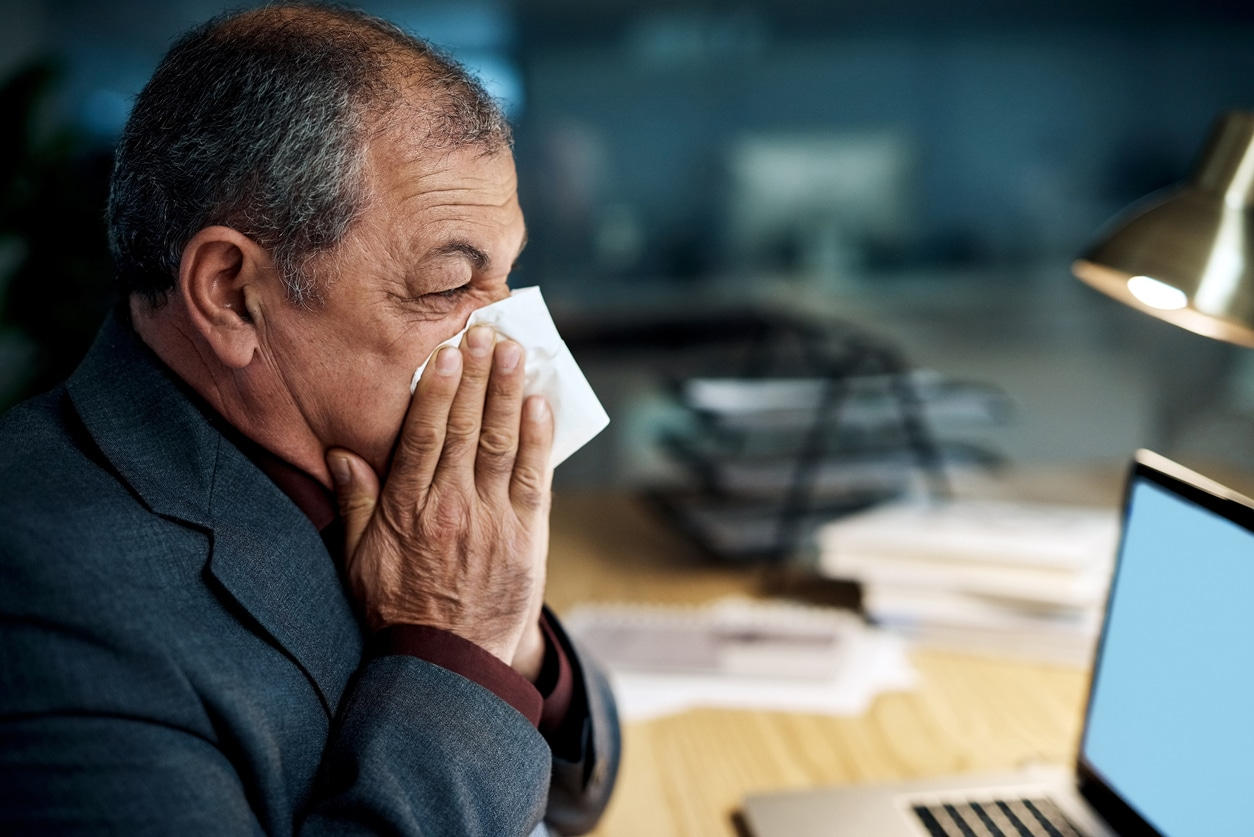 A person blowing their nose at a desk