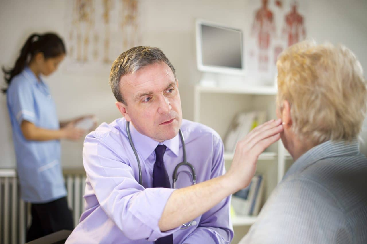 An ENT reaching out to look at a patient's ear