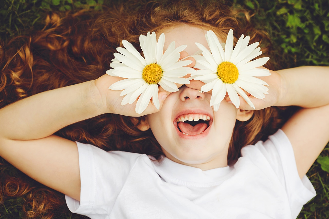 A child holding daisies up to cover their eyes
