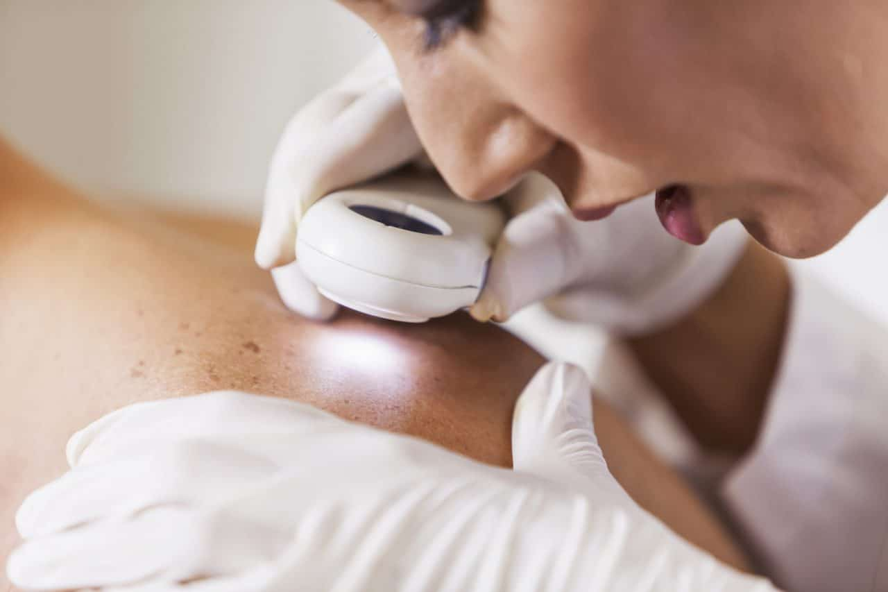 A health care provider examining a patient's spotty skin