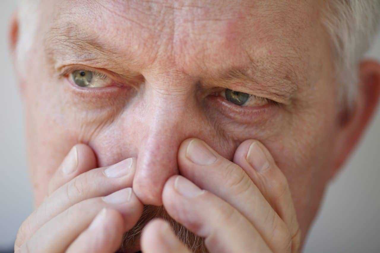 Close-up of a person holding their nose