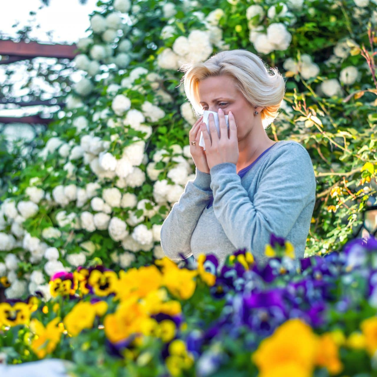 A person standing in a flower garden and blowing their nose