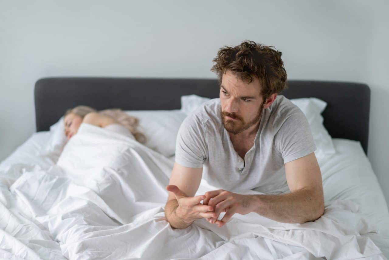 A person with rumpled hair sitting up in bed while their partner sleeps