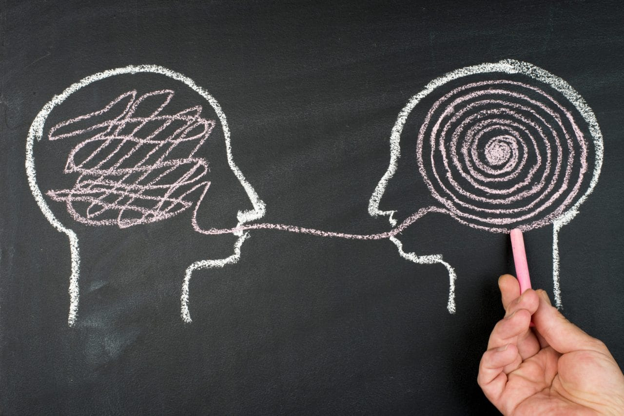 Chalk drawing of two human heads in profile, one's thoughts visualized as a neat spiral while the other's are a tangled scribble. The two are connected through a line that crosses the outline at the mouth of each head.