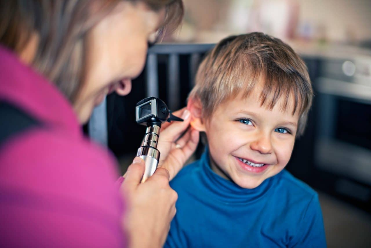 A smiling child getting an otoscope examination