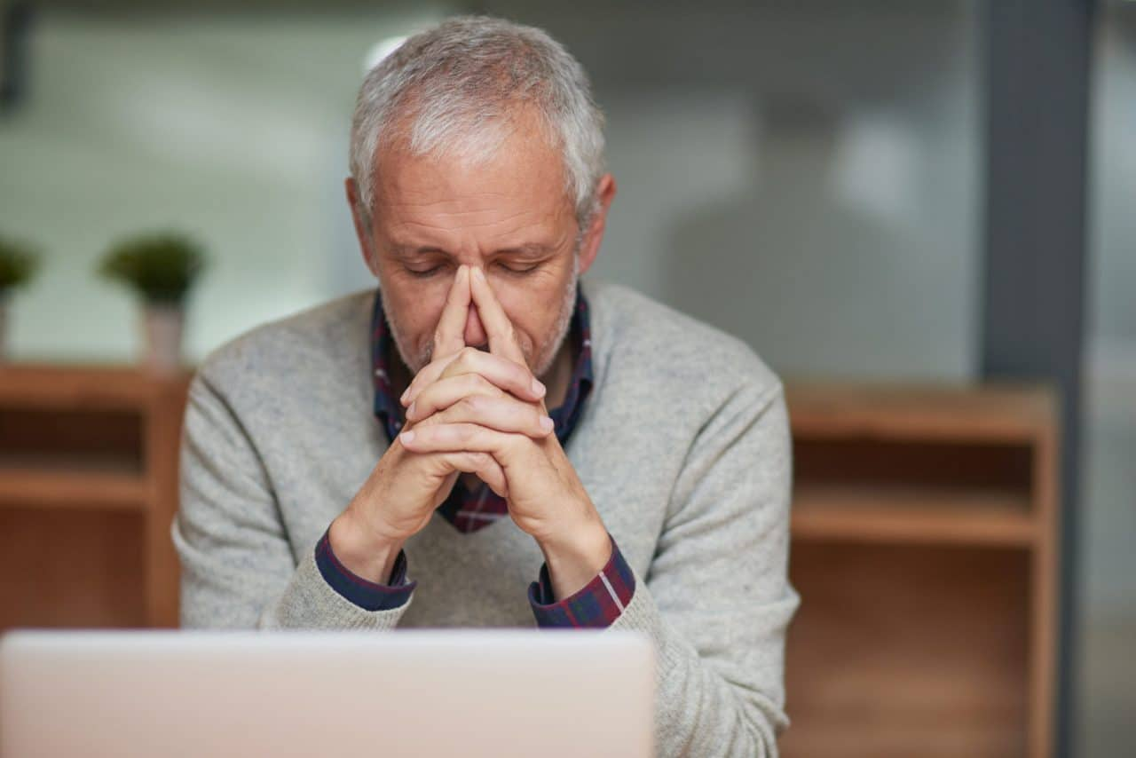 A person resting the bridge of their nose on their steepled index fingers